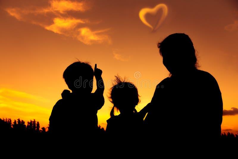 Silhueta da família feliz que senta e que olha o céu no por do sol imagem de stock royalty free