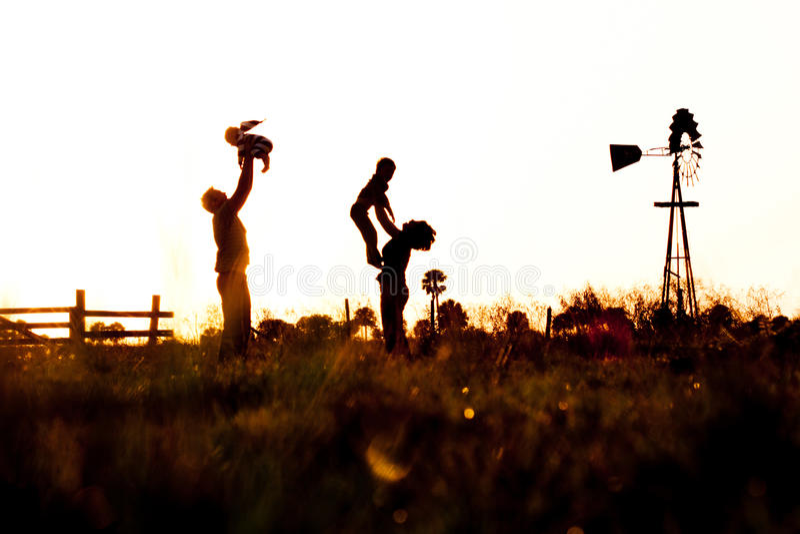 Silhueta da família no campo com moinho de vento imagem de stock