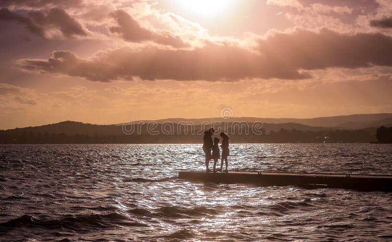 Silhueta da família que está na extremidade do molhe sob o céu dramático brilhante do por do sol imagens de stock royalty free