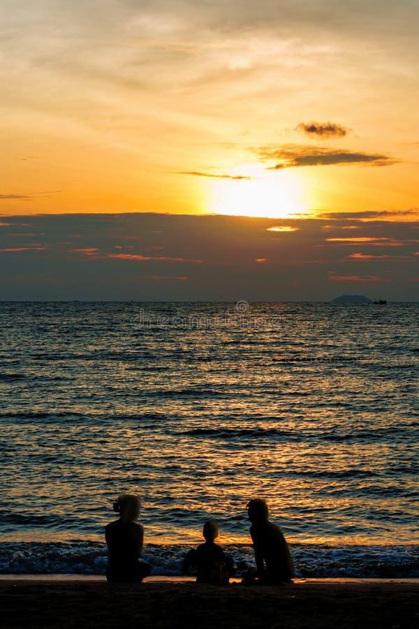 Silhueta da família que joga na praia no por do sol foto de stock