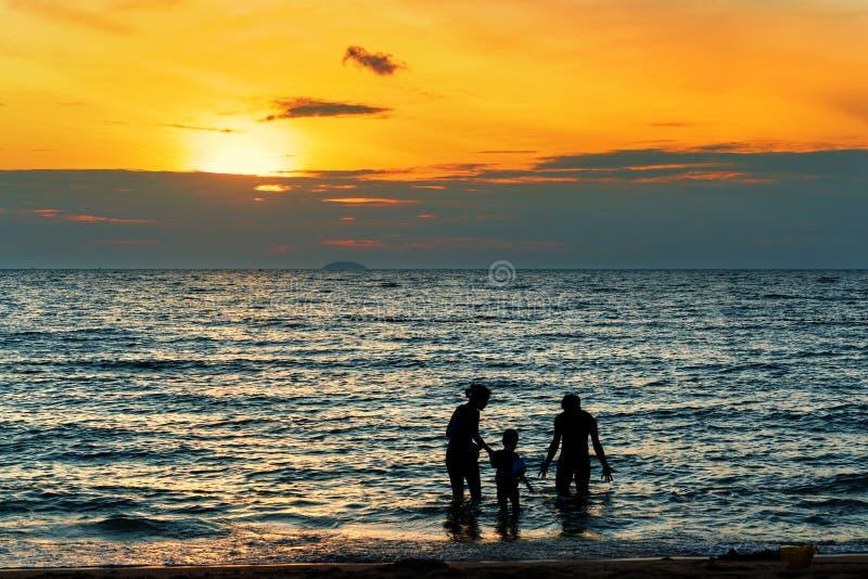 Silhueta da família que joga na praia no por do sol fotografia de stock