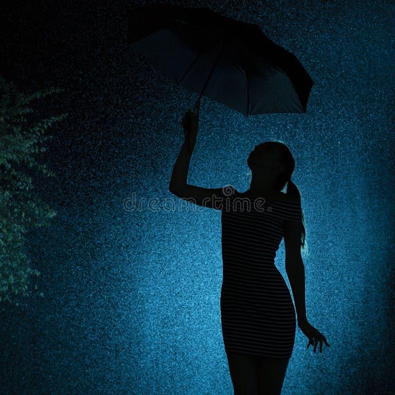 A silhueta da figura de uma moça com um guarda-chuva na chuva, uma jovem mulher com cabelo manual está feliz às gotas de fotos de stock