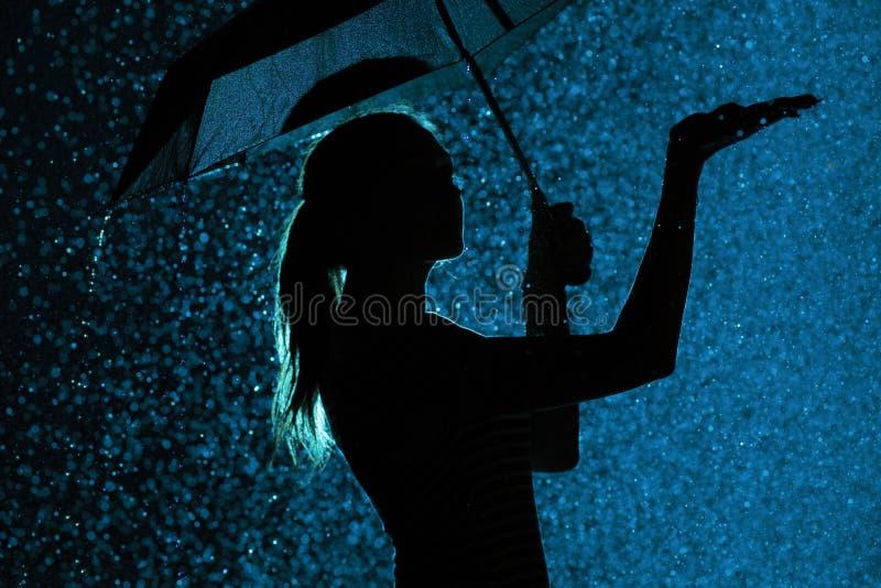 A silhueta da figura de uma moça com um guarda-chuva na chuva, uma jovem mulher está feliz às gotas da água, tempo do conceito fotografia de stock royalty free