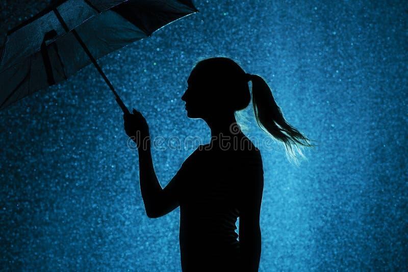 A silhueta da figura de uma moça com um guarda-chuva na chuva, uma jovem mulher está feliz às gotas da água, tempo do conceito fotografia de stock