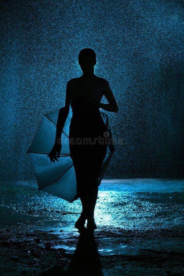Silhueta da figura de uma moça com um guarda-chuva na chuva, uma jovem mulher feliz às gotas da água imagens de stock royalty free