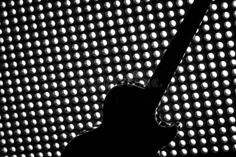 Silhueta da guitarra elétrica na grade da iluminação foto de stock royalty free