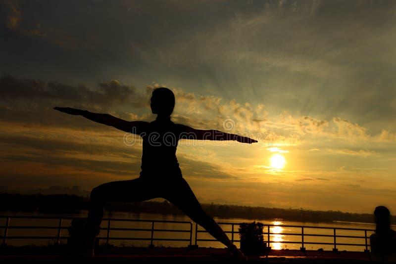 Silhueta da ioga do trem da mulher na jarda do gramado ao longo da montanha do rio imagens de stock royalty free