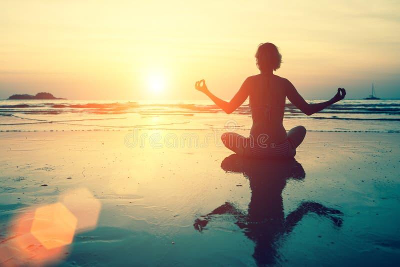 Silhueta da ioga Menina da meditação no mar durante o por do sol fotografia de stock royalty free