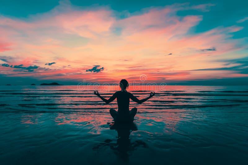 Silhueta da ioga Menina da meditação no mar durante por do sol surpreendente fotos de stock royalty free