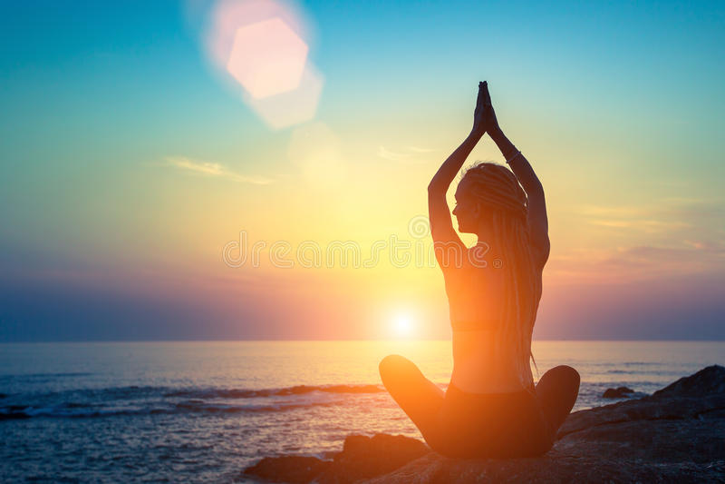 Silhueta da ioga Mulher da aptidão da meditação no oceano durante por do sol surpreendente foto de stock