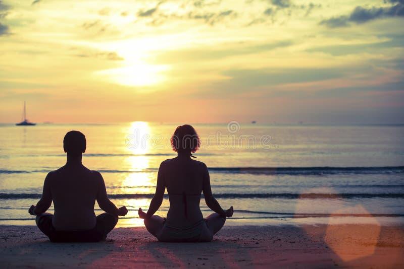 Silhueta da ioga praticando do homem novo e da mulher na posição dos lótus sobre a praia do oceano fotografia de stock royalty free