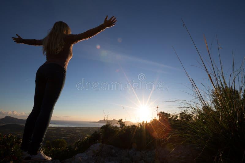Silhueta da jovem mulher com braços abertos fotografia de stock royalty free