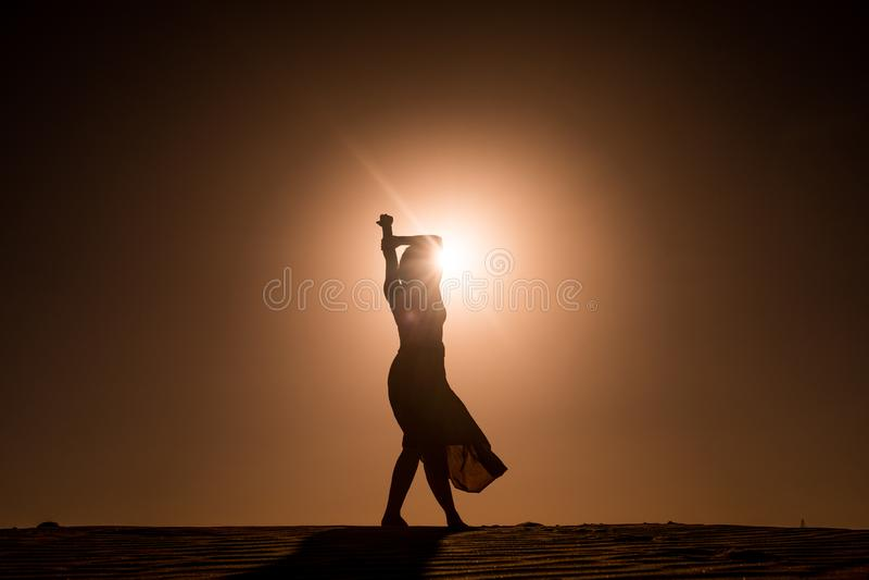 Silhueta da jovem mulher com dança longa da saia na maneira sugestiva e segura sobre a duna do deserto no por do sol com elevação foto de stock royalty free