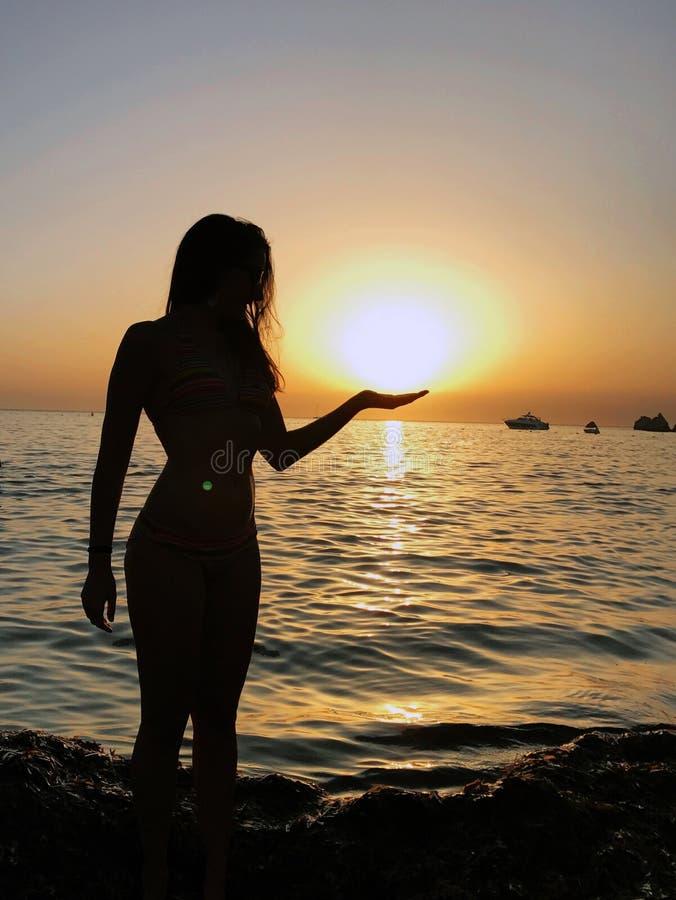 Silhueta da jovem mulher de Beaufitul em um Sandy Beach durante um por do sol imagem de stock royalty free