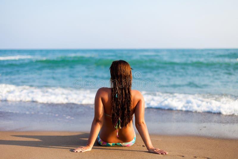 Silhueta da jovem mulher na praia Jovem mulher que senta-se na frente do beira-mar Menina no biquini que relaxa na praia Mulher fotografia de stock royalty free