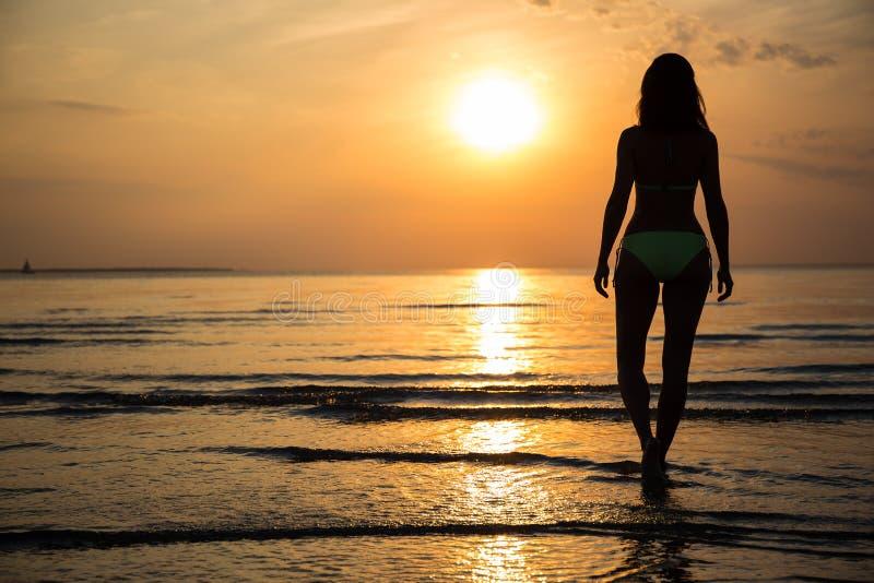 Silhueta da jovem mulher no biquini que anda na praia no por do sol fotos de stock