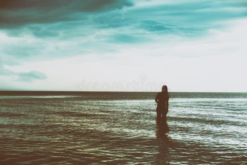 Silhueta da jovem mulher que anda no mar no por do sol foto de stock royalty free