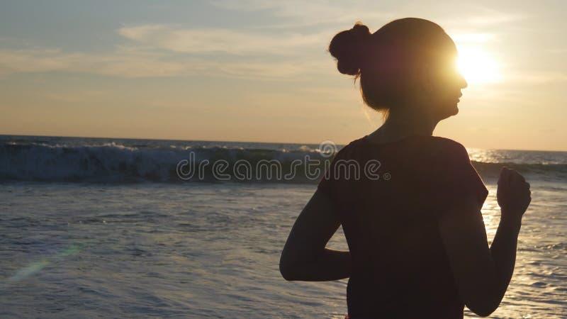 Silhueta da jovem mulher que corre na praia do mar no por do sol Menina que movimenta-se ao longo da costa do oceano durante o na foto de stock