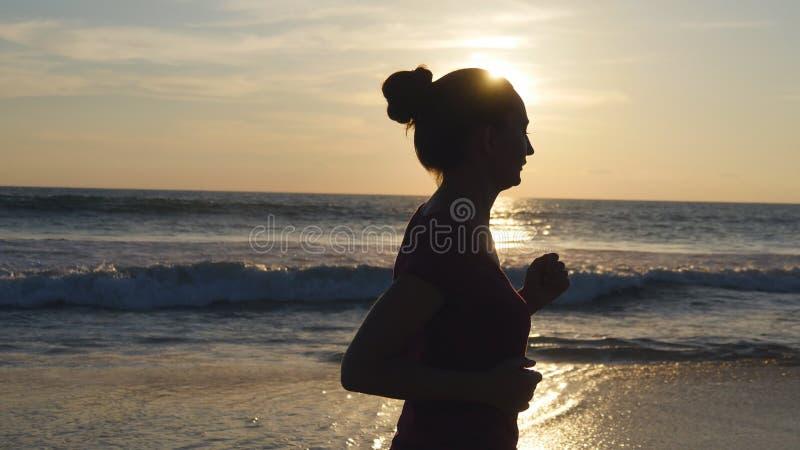 Silhueta da jovem mulher que corre na praia do mar no por do sol Menina que movimenta-se ao longo da costa do oceano durante o na foto de stock royalty free