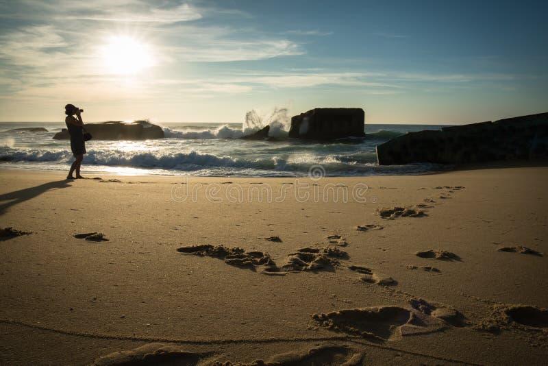 Silhueta da jovem mulher que está no Sandy Beach cênico que toma fotos do seascape bonito de Oceano Atlântico com as ondas em ens fotos de stock royalty free
