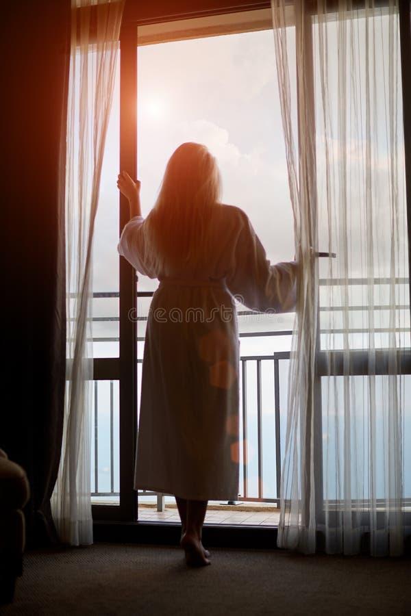 Silhueta da jovem mulher que olha para fora a janela fotografia de stock royalty free