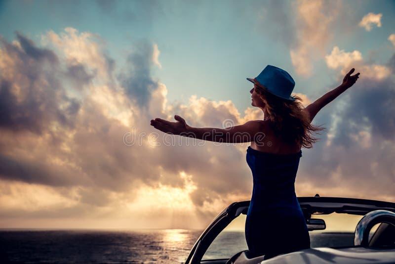 Silhueta da jovem mulher que relaxa na praia imagem de stock royalty free