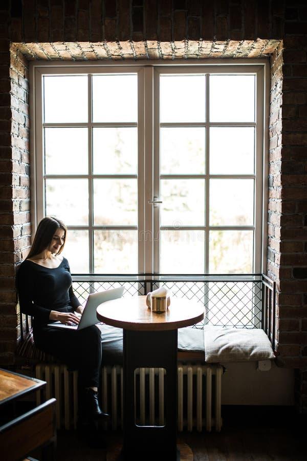 Silhueta da jovem mulher que senta-se na tabela na frente da janela e do portátil dos usos Mulher de negócios que trabalha em lin imagens de stock royalty free