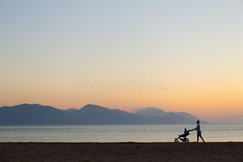 Silhueta da mãe com o passeante que aprecia a maternidade no por do sol fotografia de stock