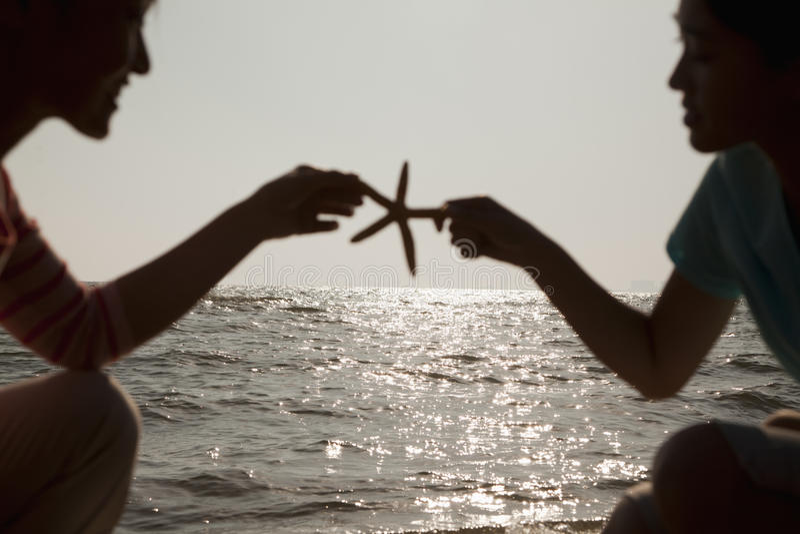 Silhueta da mãe e da filha que guardam uma estrela do mar na praia fotografia de stock