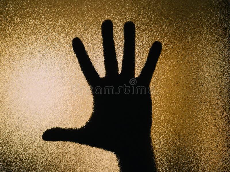 Silhueta da mão aberta em um vidro fotos de stock