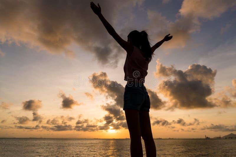 Silhueta da mão da mulher acima sob o por do sol imagens de stock