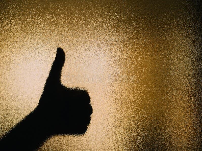 Silhueta da mão que faz os polegares acima em um vidro imagens de stock royalty free