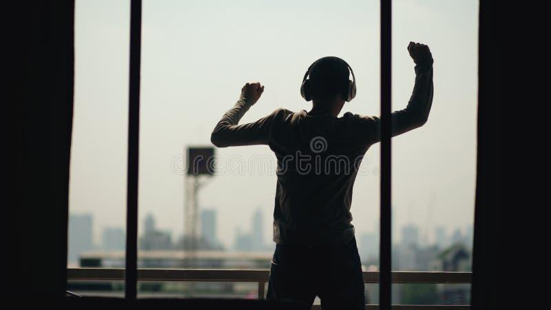 A silhueta da música de escuta do anúncio da dança do homem novo em fones de ouvido dos wireles está no balcão da sala de hotel fotografia de stock royalty free