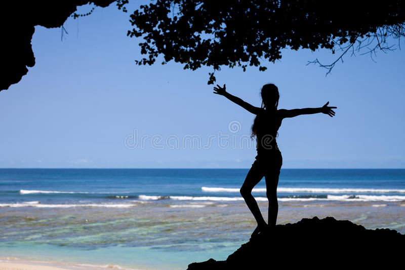 Silhueta da menina adolescente que está na praia fotografia de stock