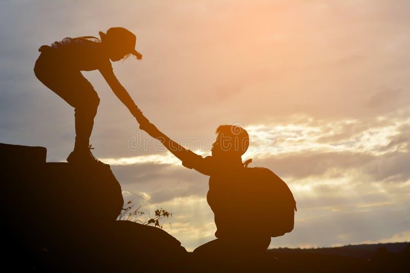 A silhueta da menina ajuda um menino na montanha foto de stock