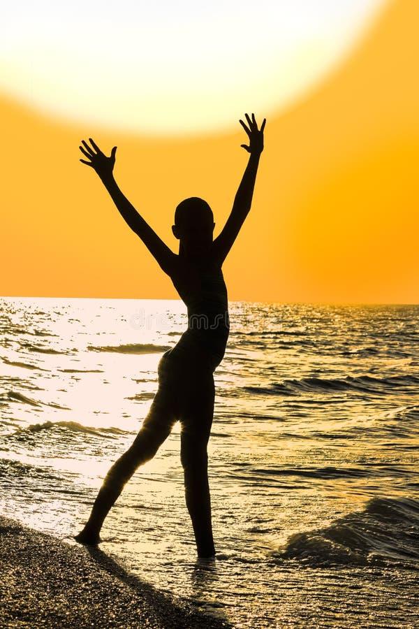 Silhueta da menina com mãos levantadas na praia no por do sol fotografia de stock