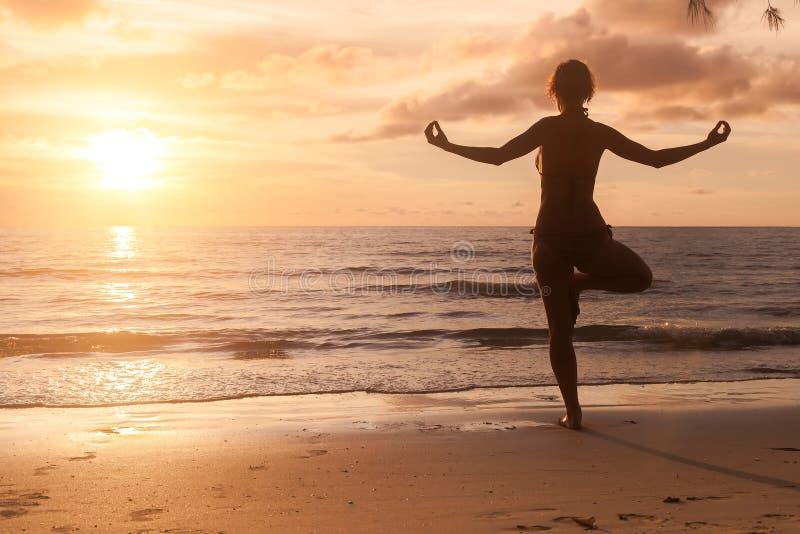 Silhueta da menina da ioga no por do sol bonito no mar nave fotografia de stock