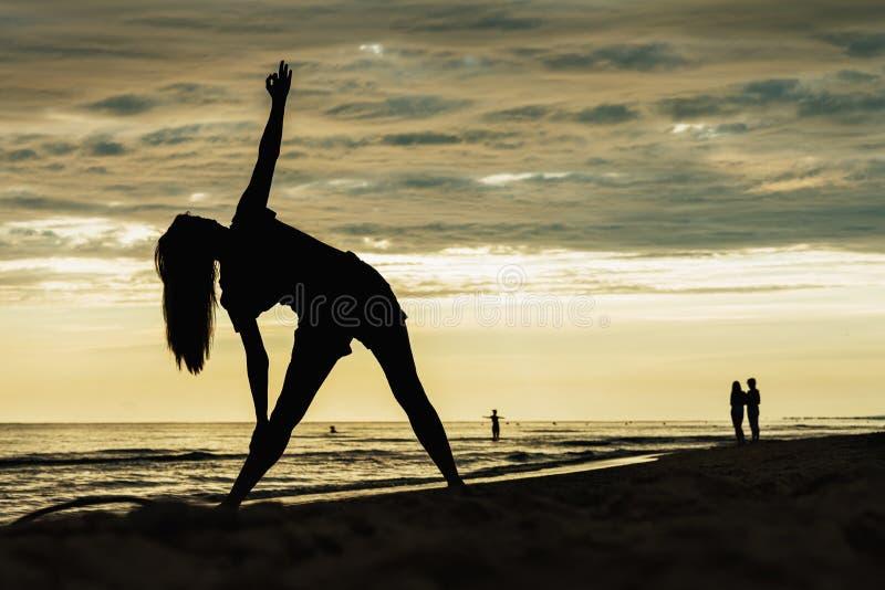 Silhueta da menina a ioga praticando no litoral fotos de stock royalty free