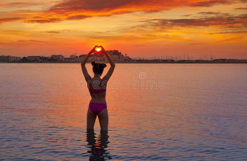 Silhueta da menina nas mãos da forma do coração do por do sol fotografia de stock royalty free