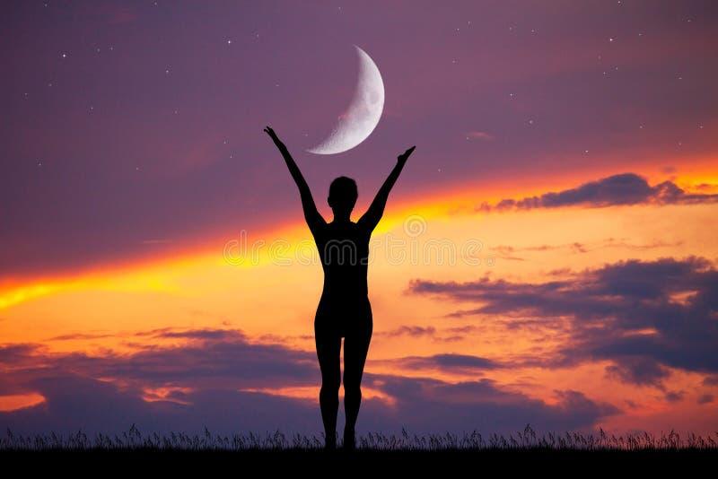 Silhueta da menina no por do sol com lua imagem de stock