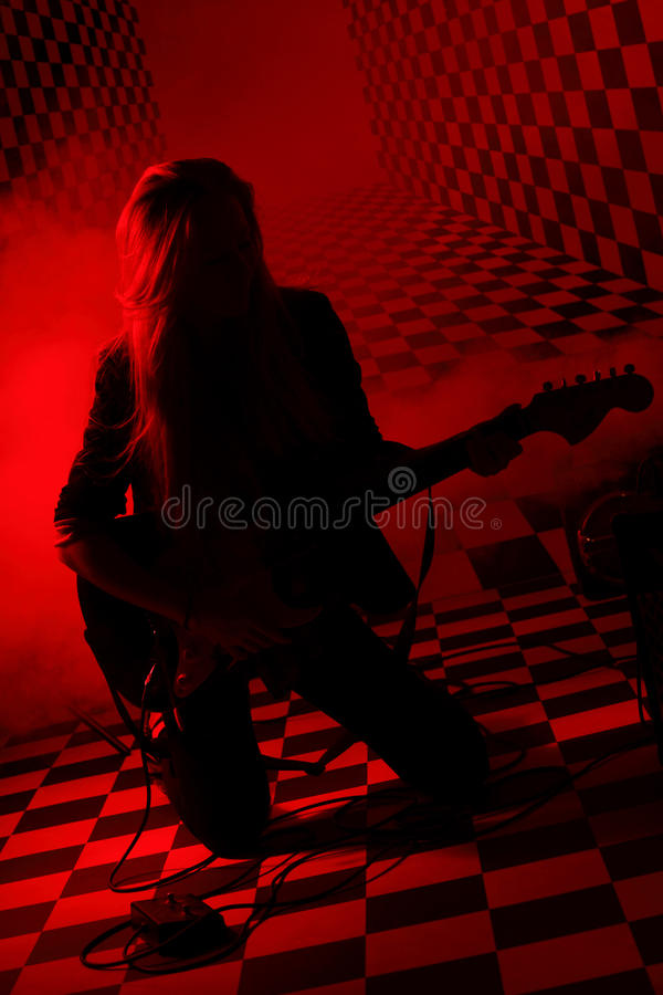 Silhueta da menina que ajoelha-se e que joga a guitarra elétrica fotos de stock royalty free