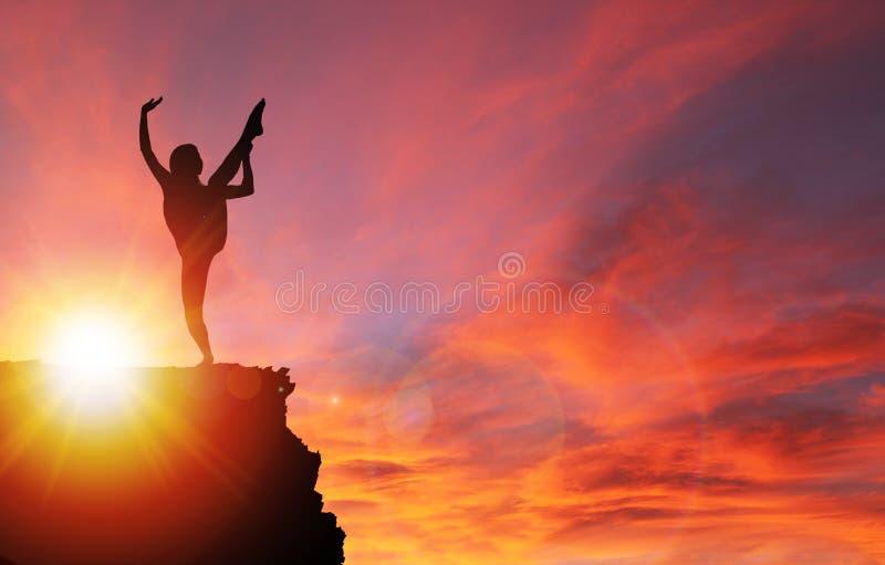 Silhueta da menina que exercita na borda do penhasco no nascer do sol foto de stock