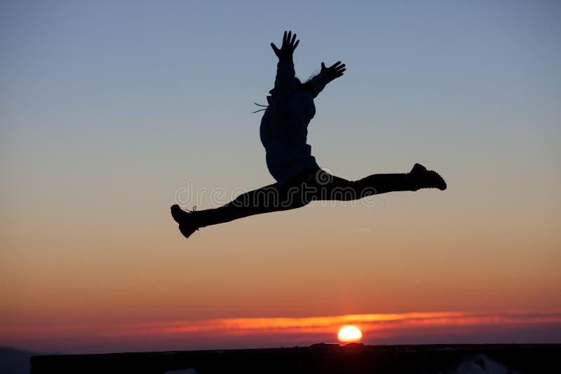 A silhueta da menina que faz as separações salta no por do sol fotos de stock royalty free