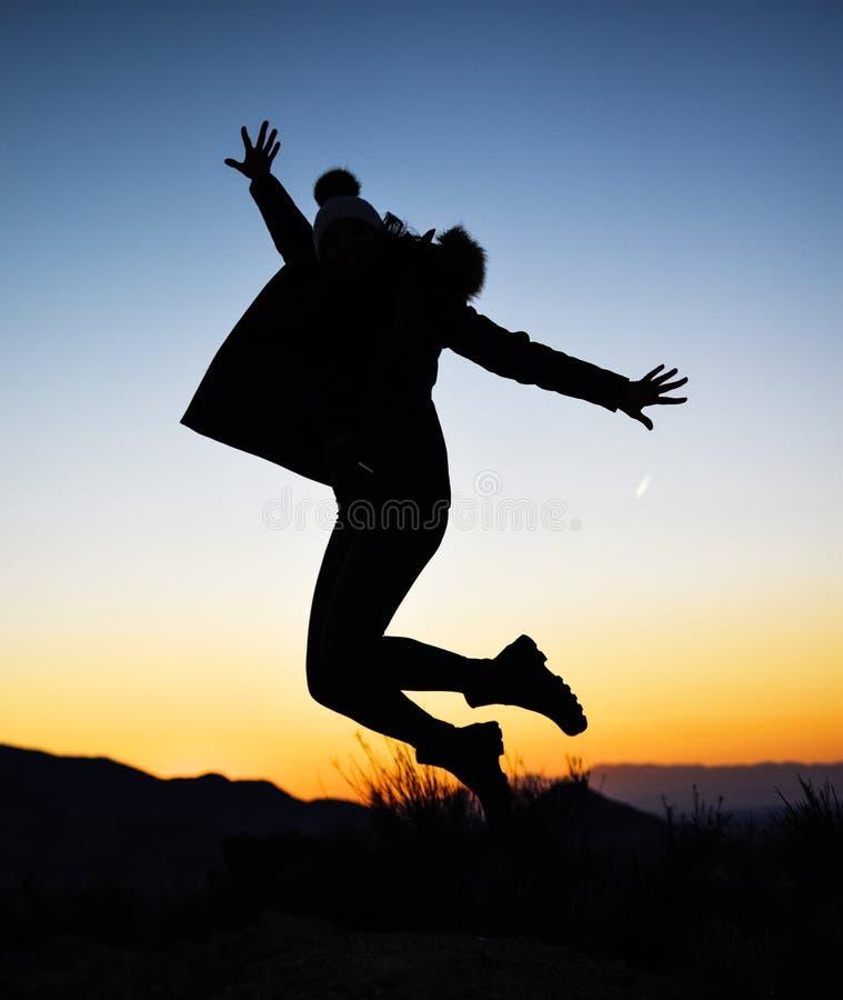 Silhueta da menina que salta no meio da natureza no inverno contra o por do sol imagem de stock