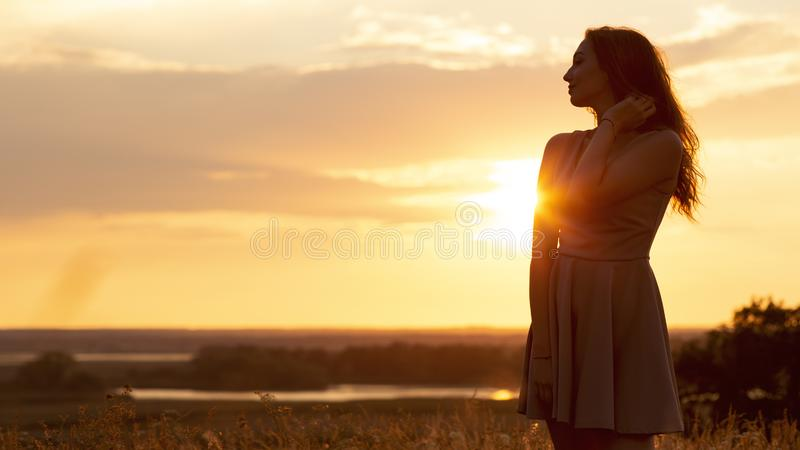 Silhueta da menina sonhadora em um campo no por do sol, uma jovem mulher em um embaçamento do sol que aprecia a natureza, estilo  imagem de stock