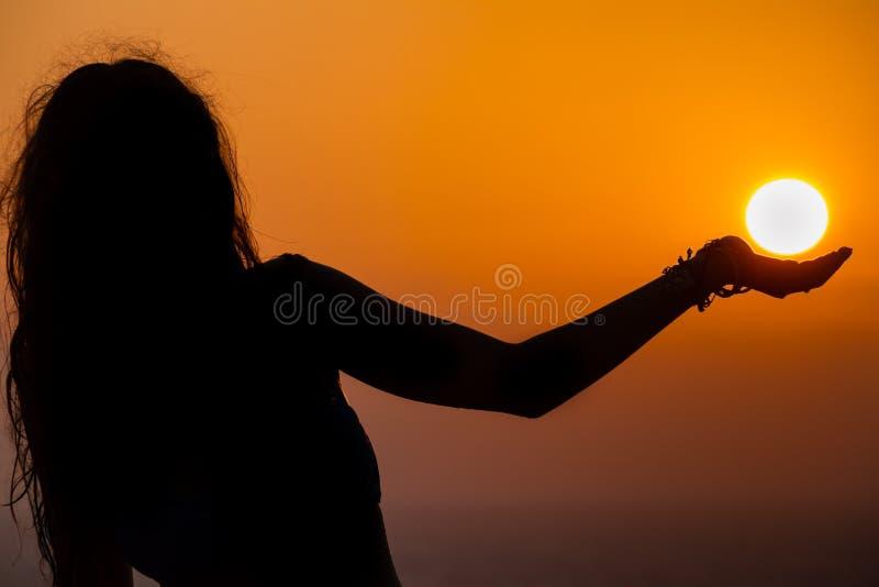 Silhueta da menina, sua palma que parece apoiar o sol como foto de stock