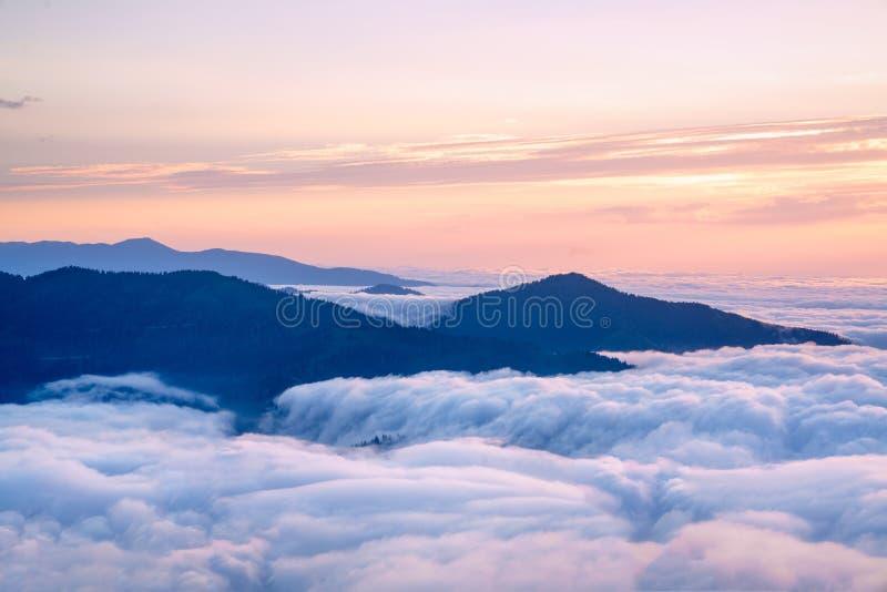 Silhueta da montanha acima das nuvens no nascer do sol, vista do t imagem de stock