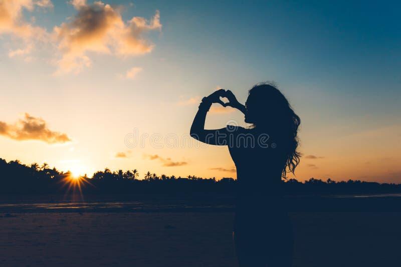 Silhueta da morena 'sexy' no roupa de banho que faz gestos de mão, mostrando o amor no por do sol imagem de stock