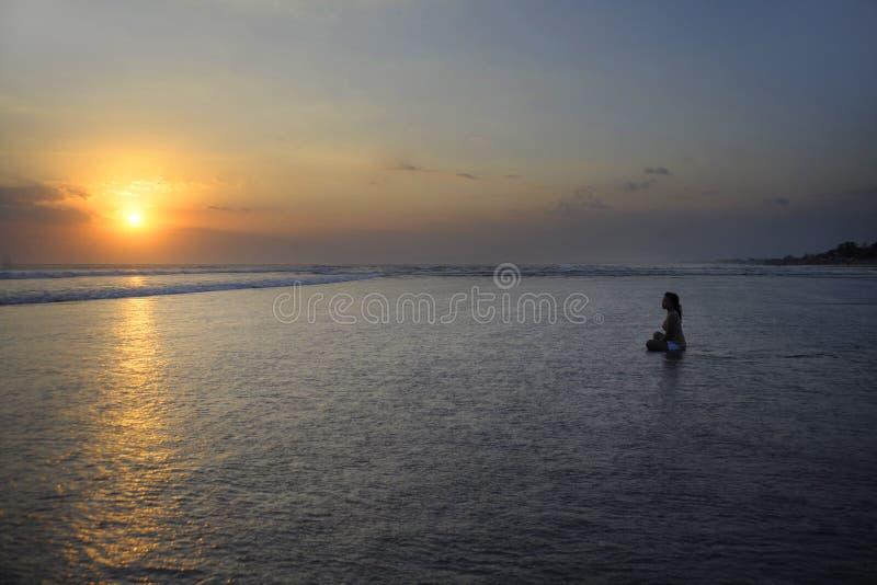 Silhueta da mulher asiática bonita nova que senta-se na água da areia livre e relaxado olhando o sol na praia do por do sol imagem de stock royalty free