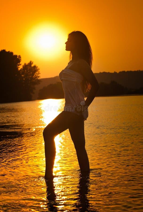 Silhueta da mulher bonita nova no rio sobre o céu do por do sol Contorno perfeito fêmea do corpo na praia no cenário crepuscular imagens de stock